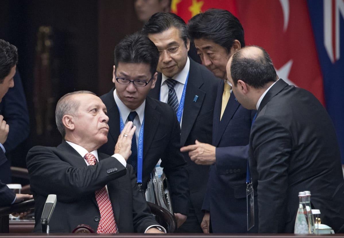 Erdoğan istuu, miehet ympärillä seisovat.