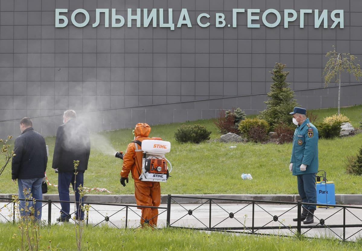 Sairaalan edustalla desinfioidaan ihmisiä Pietarissa