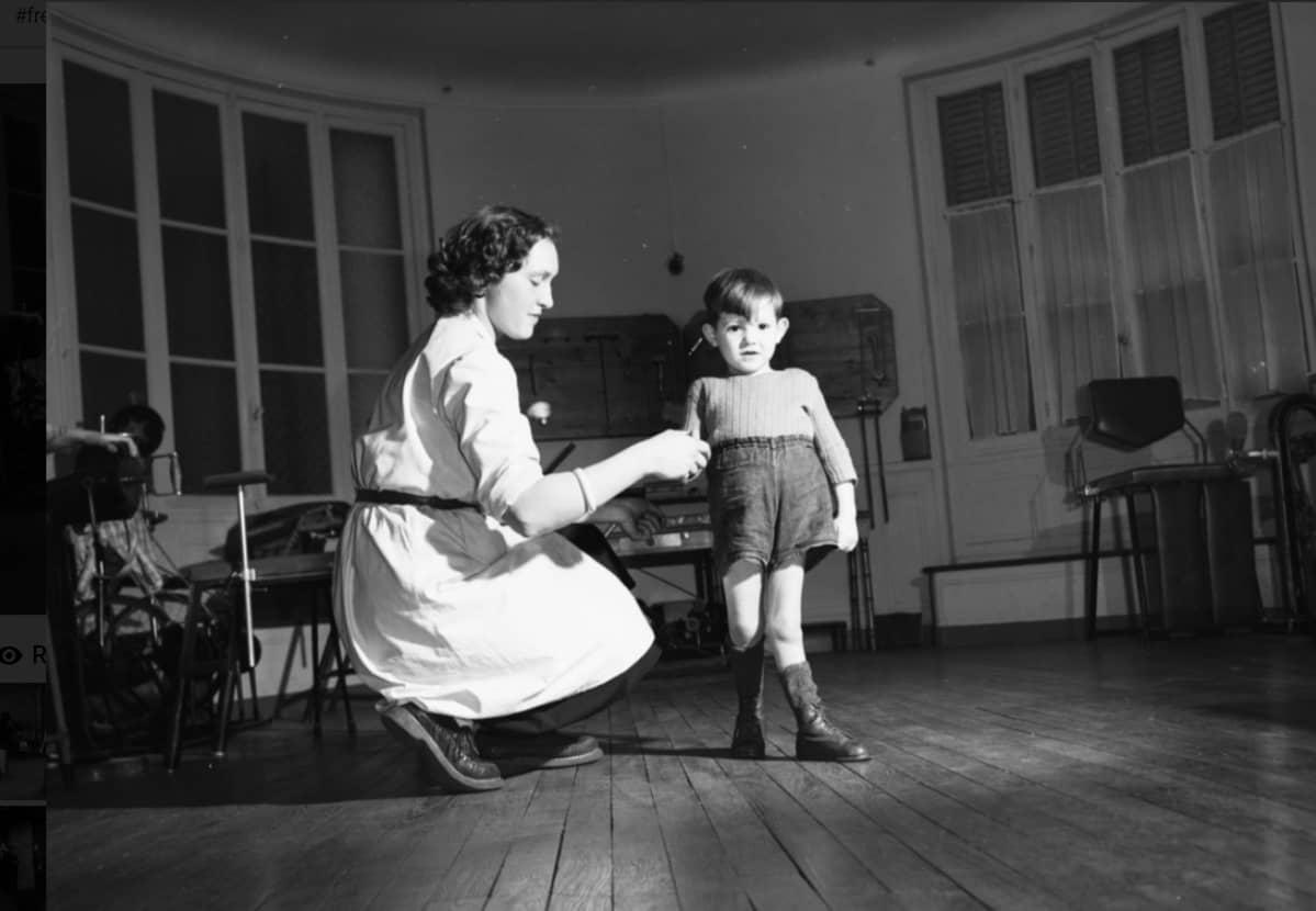 Mustavalkoinen kuva pikkupojasta, jonka toinen jalka on halvaantunut.  Hoitaja on kyykistynyt hänen viereensä.