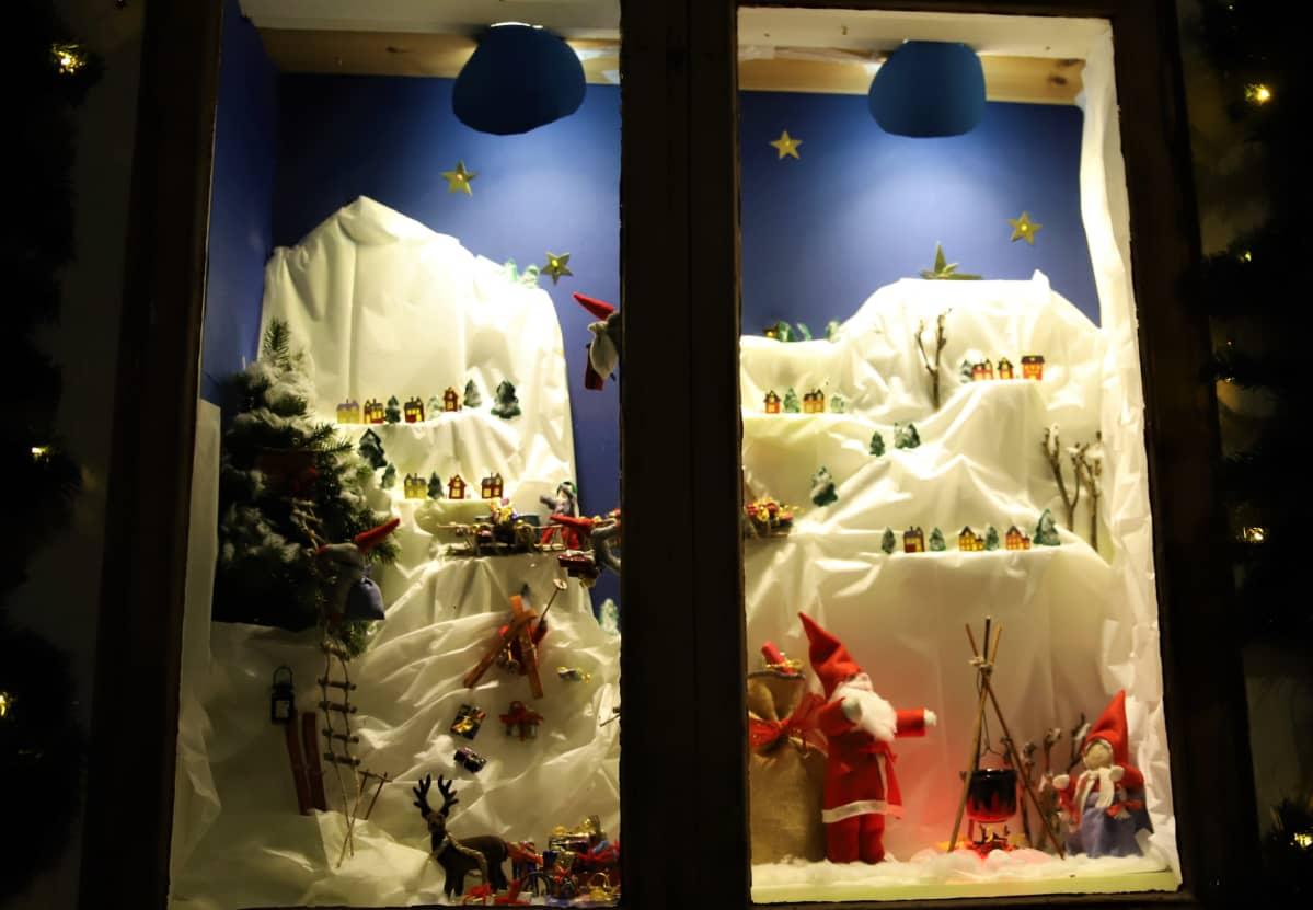 joulupukki, taloja ja muita koristeita ikkunassa