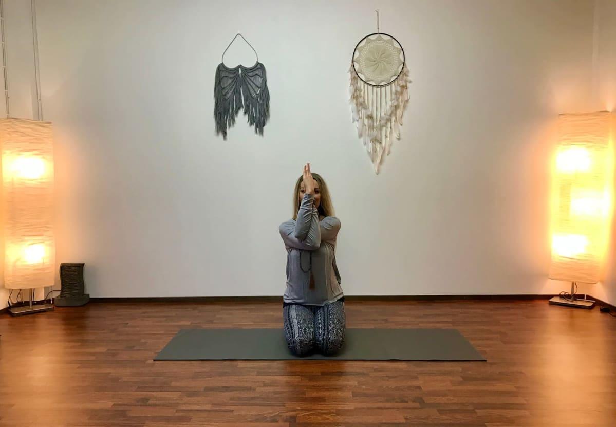 Nainen joogamatolla polviensa päällä asanassa