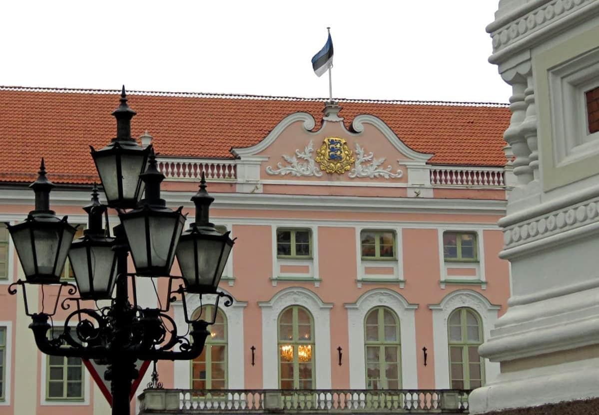 Riigikogun vaaleanpunainen talo, jonka katolla liehuu Viron lippu. Etualalla katedraalin nurkka sekä lyhtypylväs.