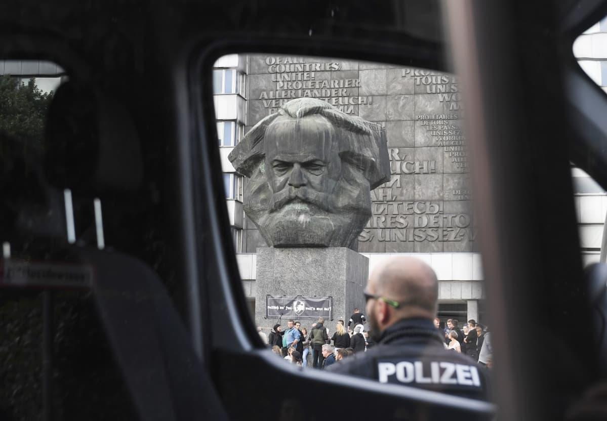 Poliisiauton ikkunan läpi otettu kuva. Etualalla auton luona seisoo kaljupäinen parrakas poliisimies. Aukiolla näkyy jylhän betoninen Karl Marxin pää.