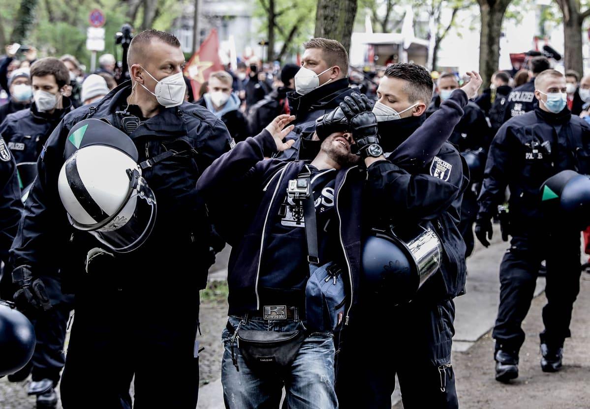 Poliisi kiinniottaa koronarajoituksia vastustavaa mielenosoittajaa.