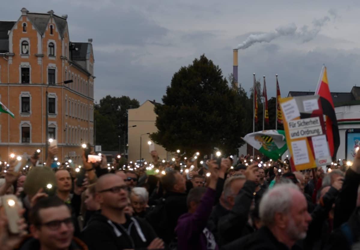 Joukko mielenosoittajia. Kännykät loistavat kuin kynttilät pimenevässä illassa.