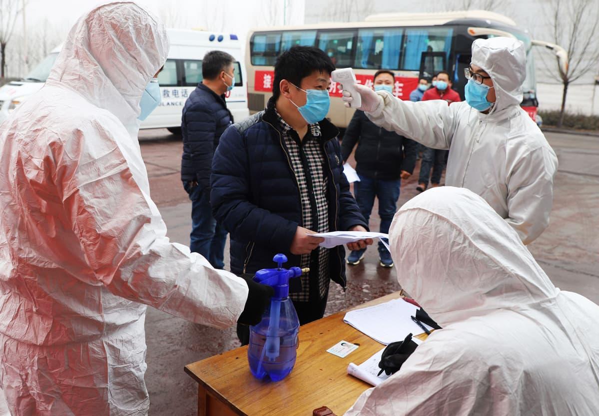 Kiinassa Shandongin maakunnassa mitataan työntekijän lämpötilaa helmikuun lopulla.