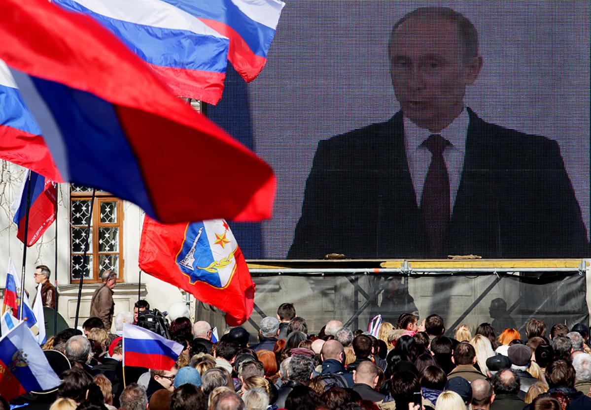 Väkijoukko seuraa Vladimir Putinin puhetta suurelta videonäytöltä Sevastopolissa.