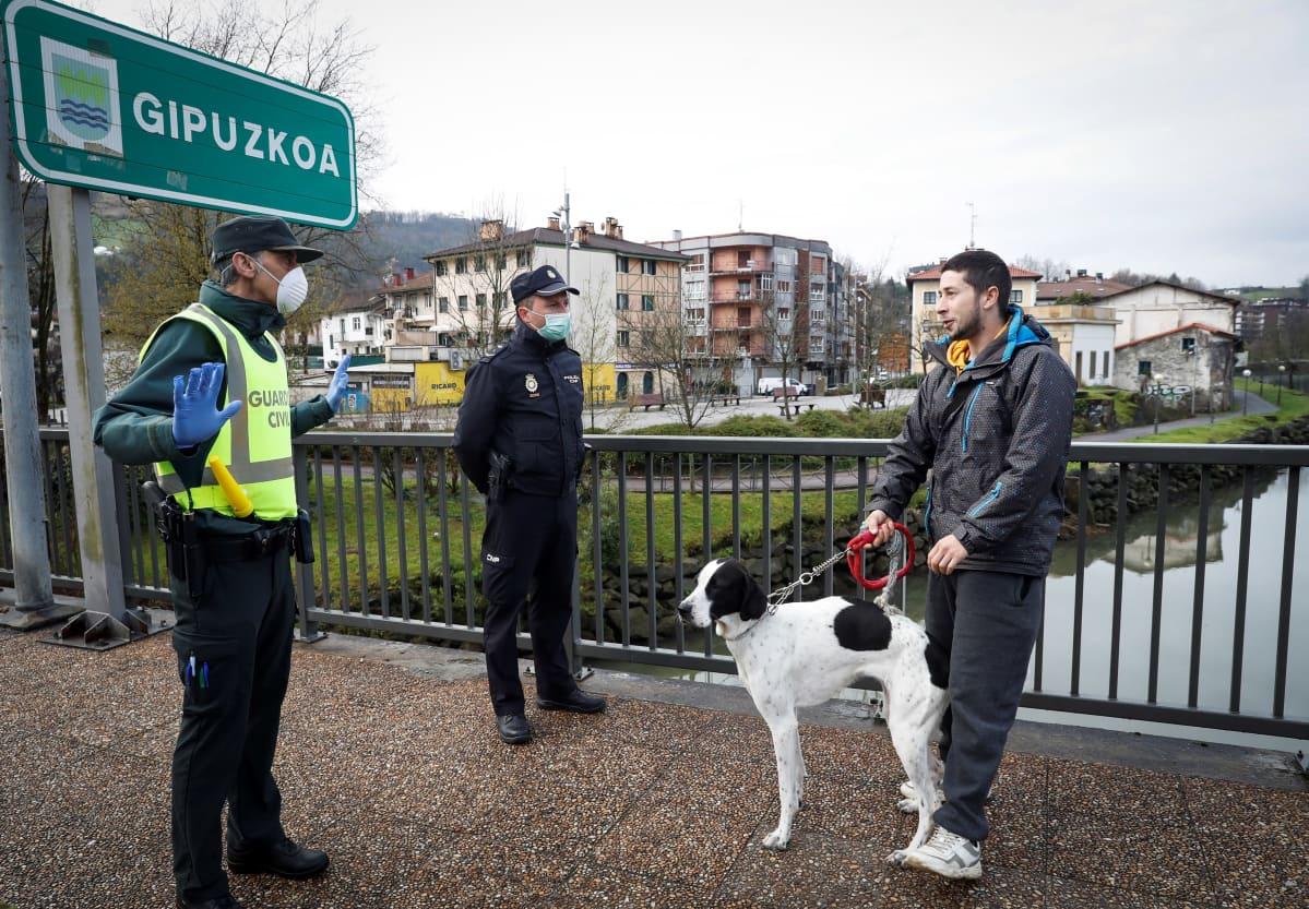 Poliisi pysäyttämässä koiran kanssa liikkuvaa miestä rajasillalla.