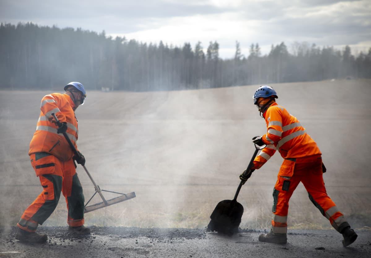 Kaksi miestä tekee asfalttitöitä Lohjalla Koisjärven kylässä.