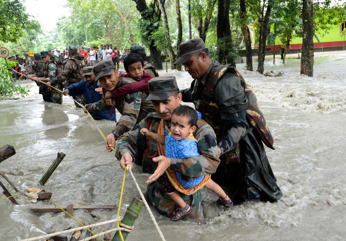 Intian armeijan sotilaat auttavat ihmisiä ylittämään tulva-aluetta Nalbarissa, Intiassa 24. heinäkuuta.