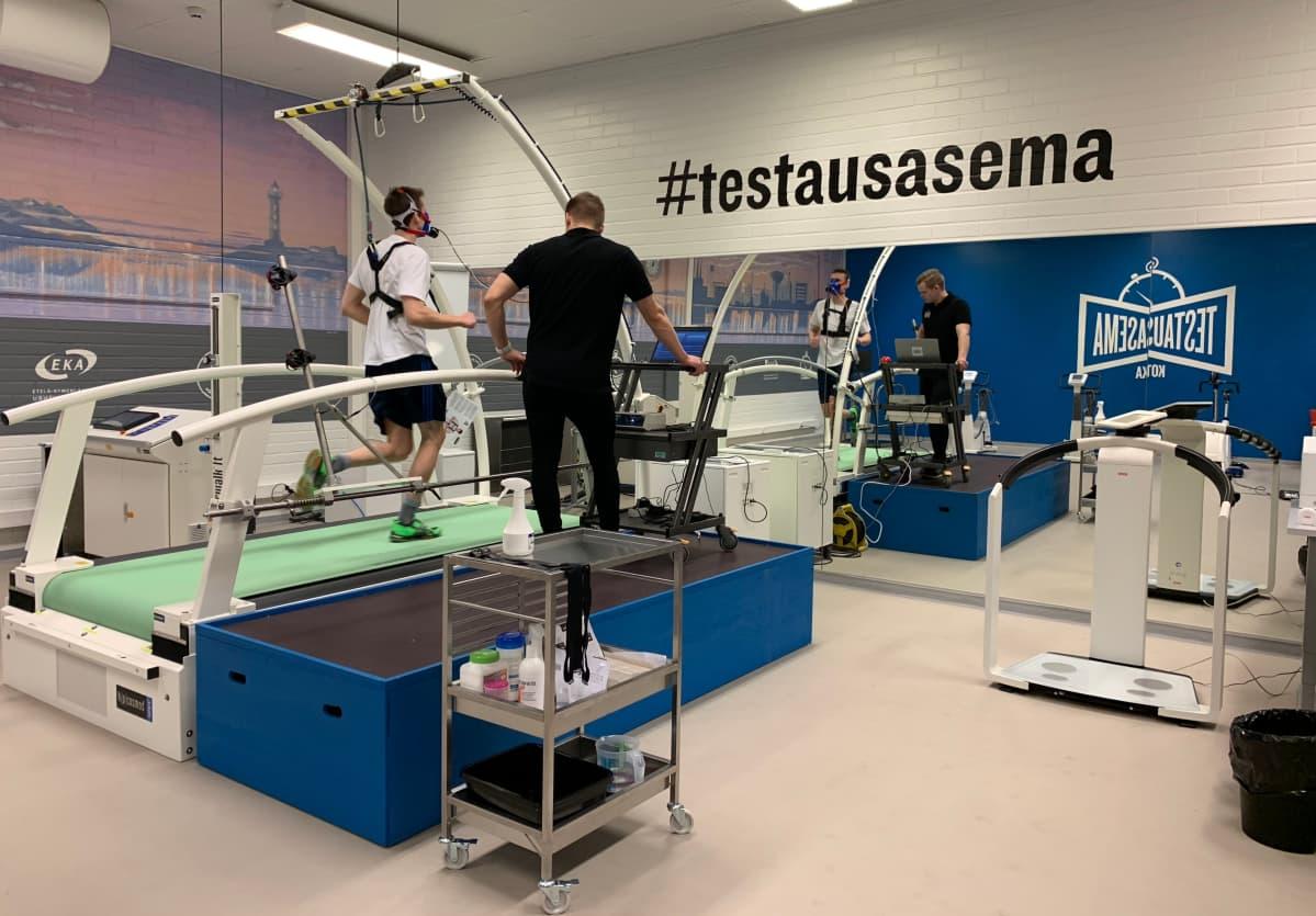 Tapani Laakso juoksee juoksumatolla hengityskaasuanalysaattori kasvoillaan Kotkan uudella testausasemalla.