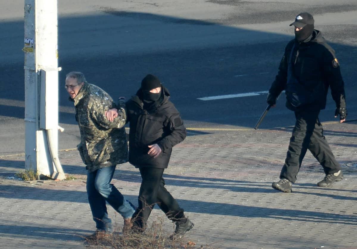 Poliisi ottaa kiinni mielenosoittajaa.