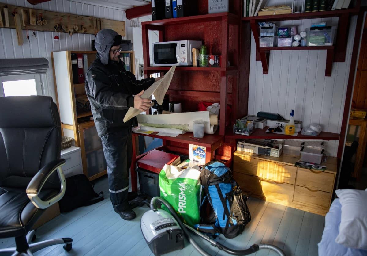 Timo Ruuska tutkimassa karttaa toimistossansa.