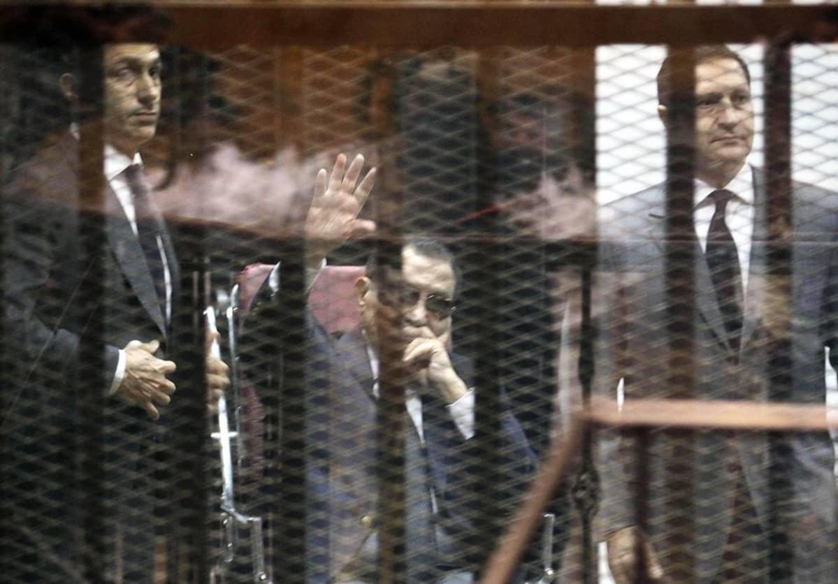 Istuva Hosni Mubarak nostaa kättään häkissä, pojat seisovat kummallakin puolella.