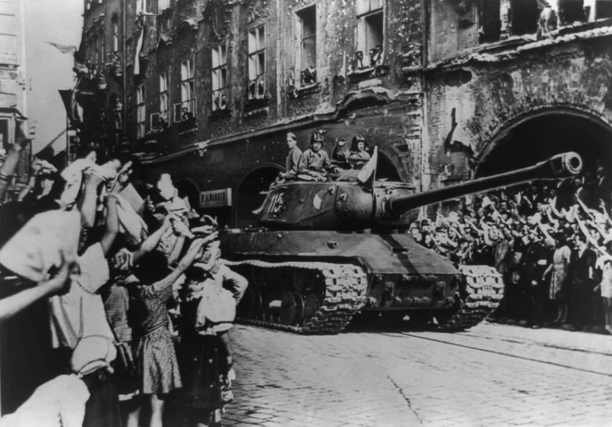 Panssarivaunu etenee kadulla, ihmiset vilkuttavat jalkakäytävillä