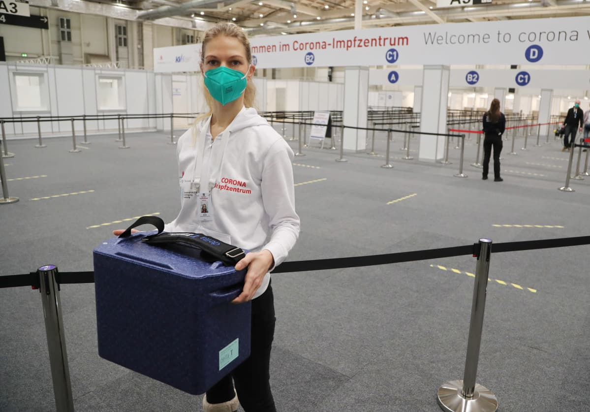 Rokotuskeskuksen työntekijä kantaa kylmälaukkua keskuksen sisääntuloaulassa
