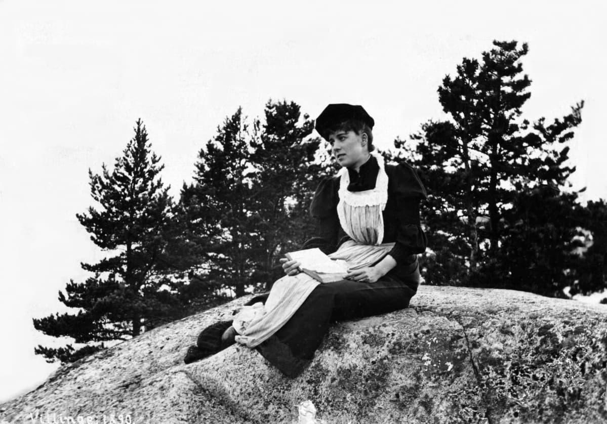 Kuvassa Unon vaimo Ellen istuu kalliolla v 1890