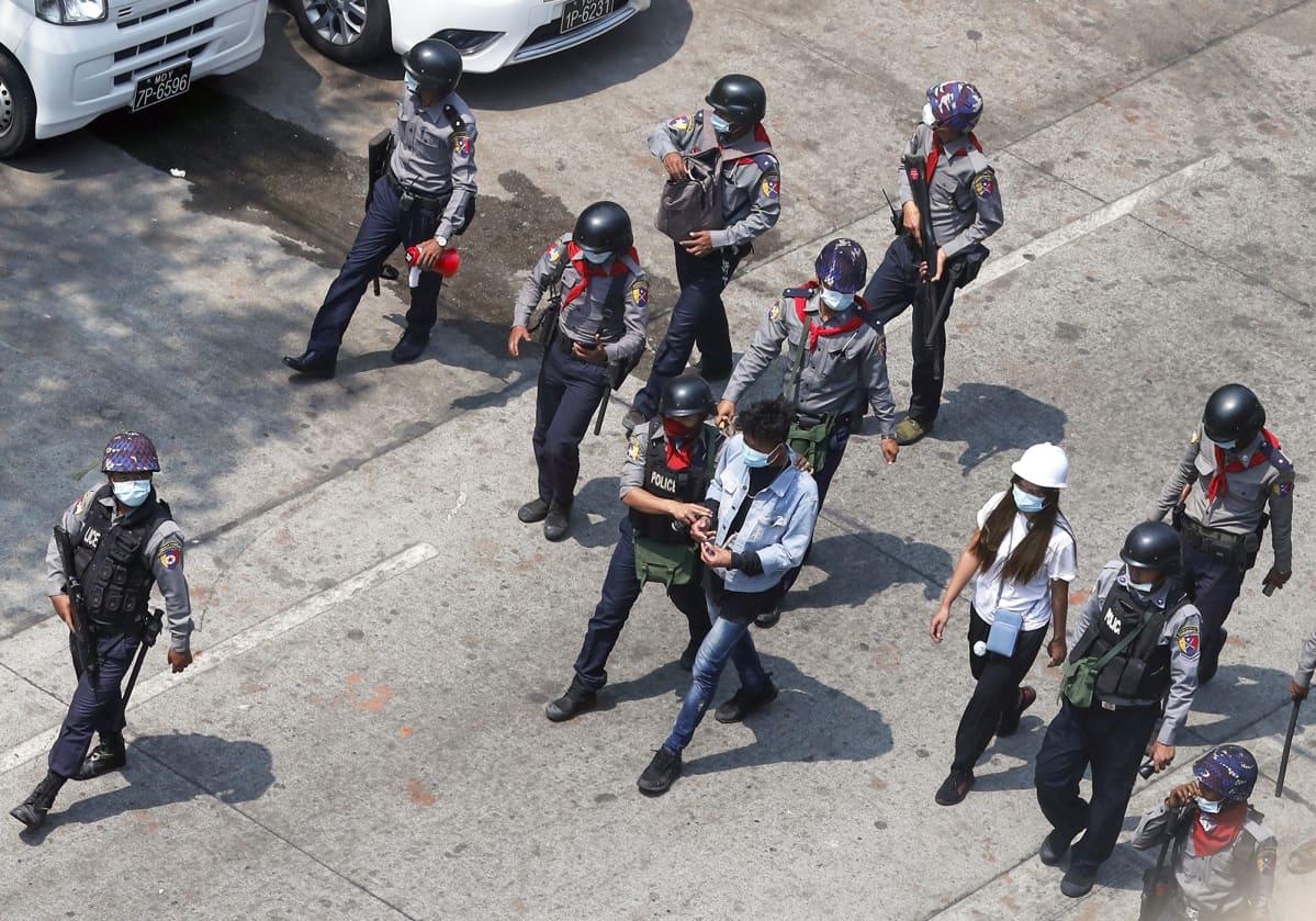 Poliisit taluttavat pidätettyä mielenosoittajaa kadulla.