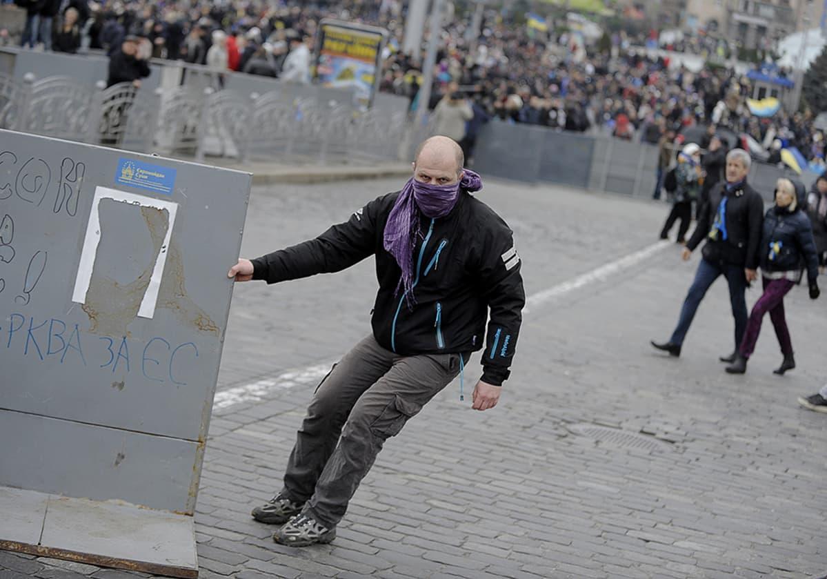 Mielenosoittajat raivaavat poliisin asettamia mellakka-aitoja Itsenäisyysaukiolla.