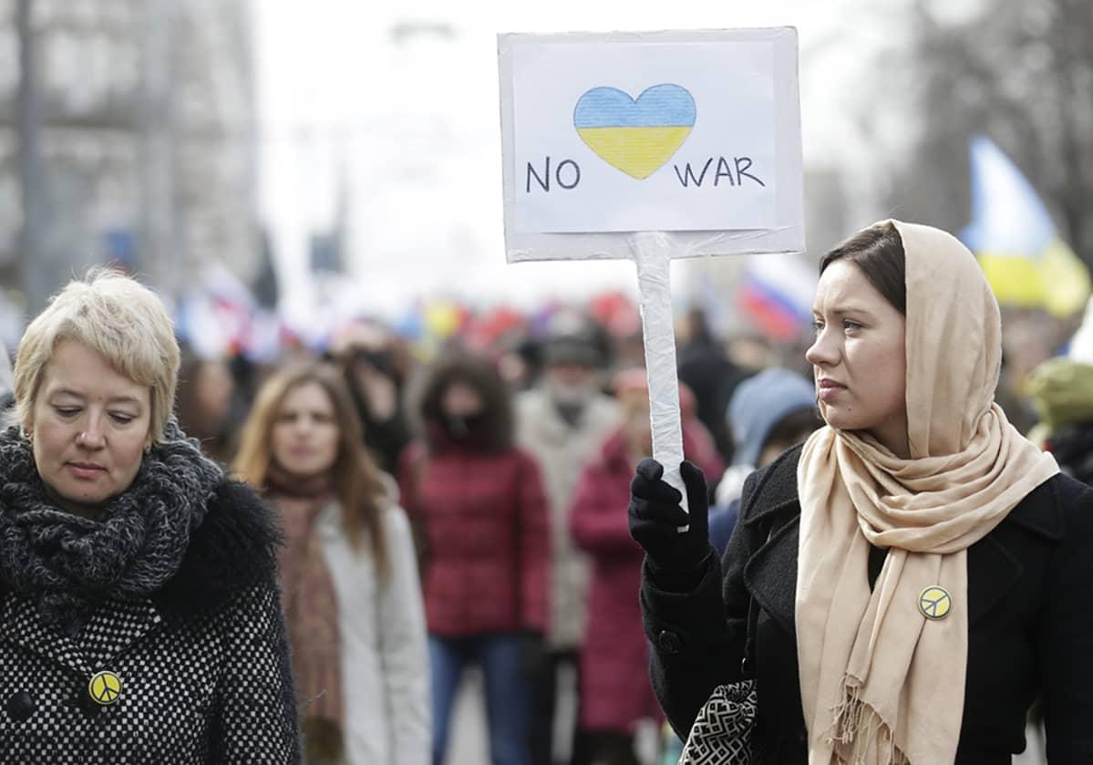 Nainen pitelee No war -kylttiä.