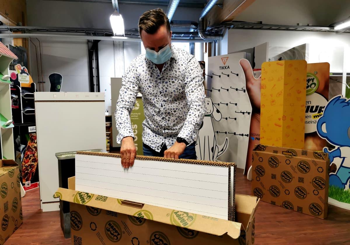 Juha Hepokorpi nostaa pahvista messuosastoa laatikosta ulos