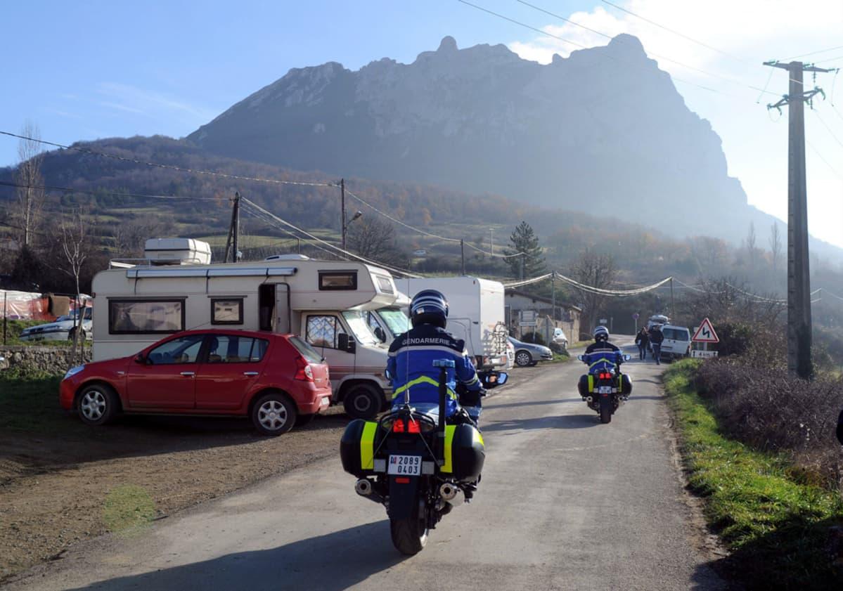 Ranskalaiset santarmit partioivat  Bugarach-vuorelle johtavalla tiellä, jonka varteen on pysäköity matkailuautoja. Vuoren uskotaan olevan maailman ainoa paikka, johon lähestyvää maailmanloppua voi paeta.
