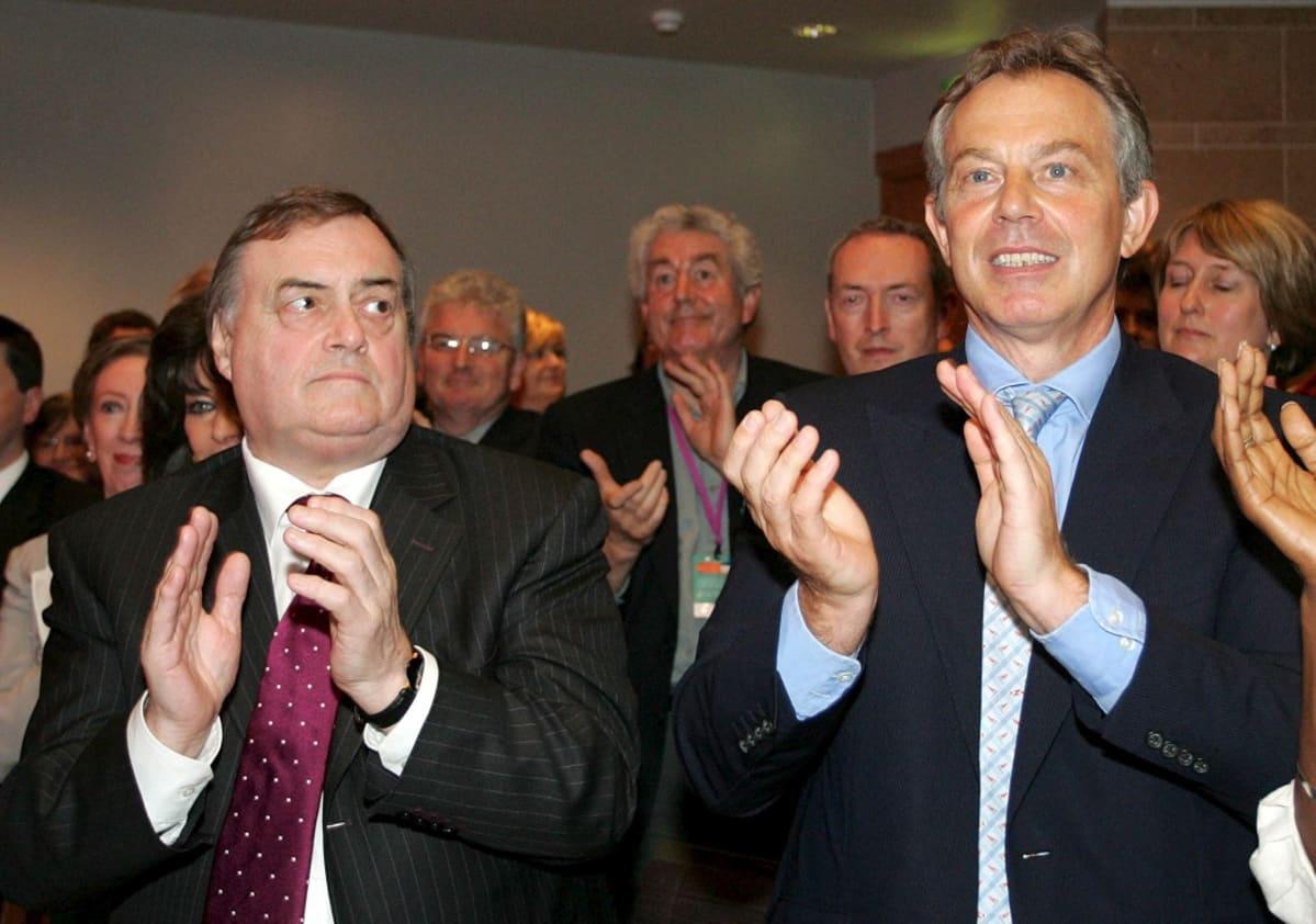 Blair ja Prescott seisovat yleisössä ja taputtavat. Prescott katsoo Blairia, joka puolestaan katsoo lavalle päin.