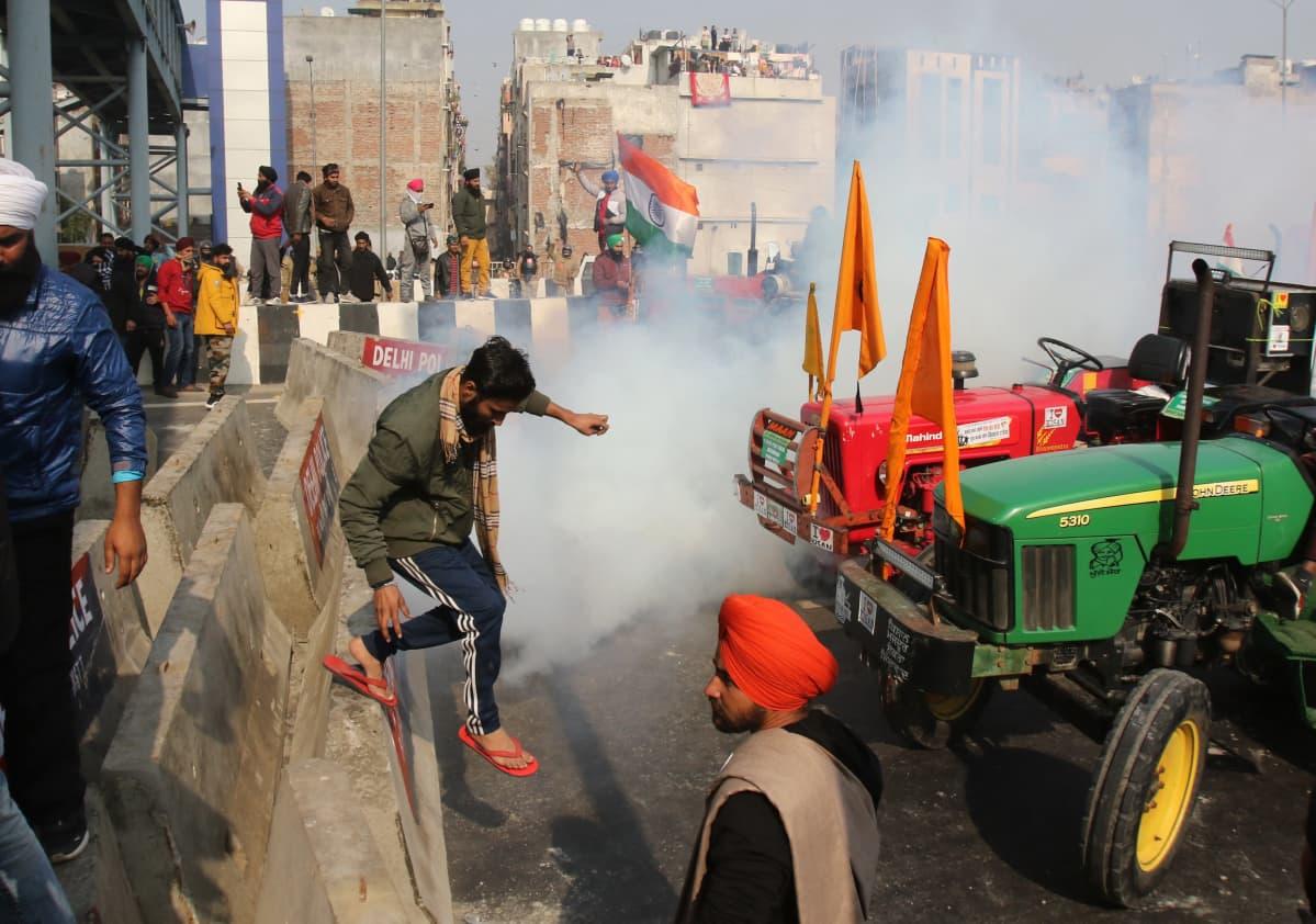 Mielenosoitusta Noidan kaupungissa Intiassa. Kyynelkaasu leviää maisemassa. Vihreätakkinen mies on juuri hyppäämässä betoniselta korokkeelta kadulle, jossa seisoo kaksi traktoria, vihreä ja punainen, oransseilla lipuilla koristeltuina.