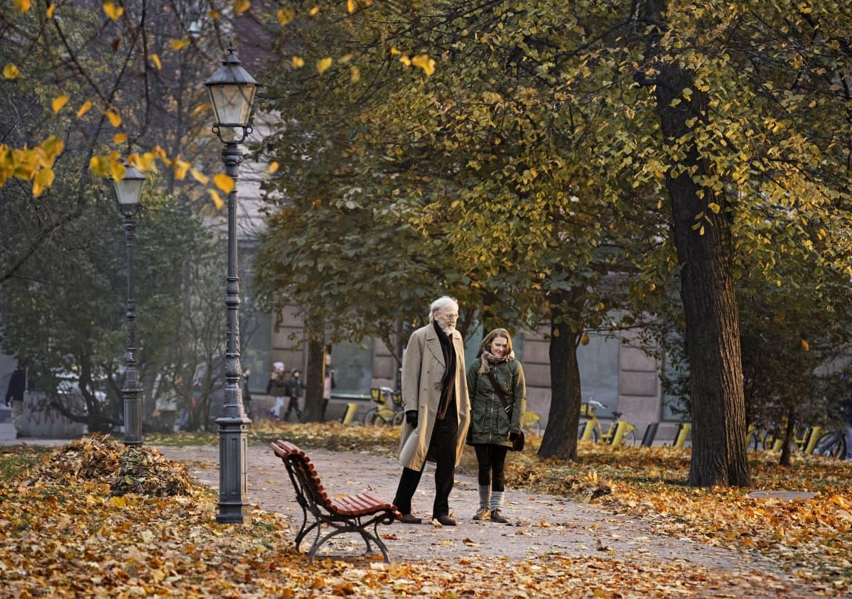 Olavi (Heikki Nousiainen) och Lea (Pirjo Lonka) promenerar tillsammans i en höstlig park.