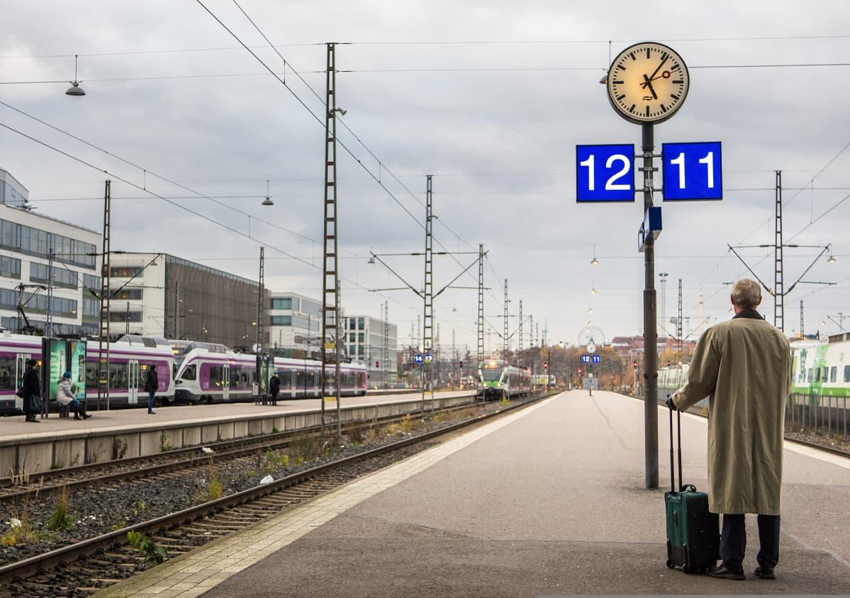 Mies odottaa matkalaukun kanssa laiturilla kello alla junaa.