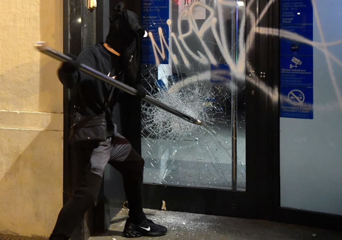 Mellakoitsija särkee pankin ikkunaa Barcelonassa.