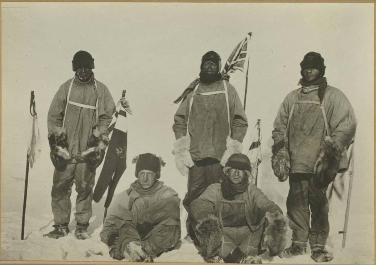 Kellertävä valokuva viidestä 1900-luvun alun retkivaatteisiin pukeutuneesta, pakkasen puremasta miehestä lumihangessa.