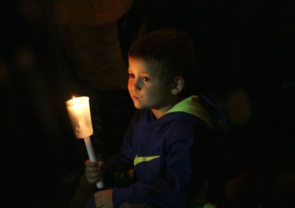Pikkupoika kantaa pimeässä kynttilälyhtyä.