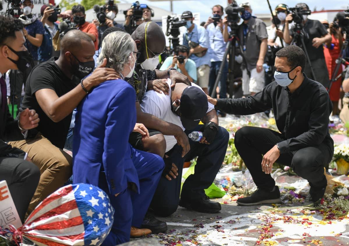 Ihmisiä polvistuneina kadulla. Poliisin surmaaman George Floydin veli Terrence Floyd (valkoisessa paidassa) vieraili veljensä kuolinpaikalla Minneapolisissa maanantaina. Kadunpätkälle on tuotu runsaasti kukkia George Floydin muistoksi.