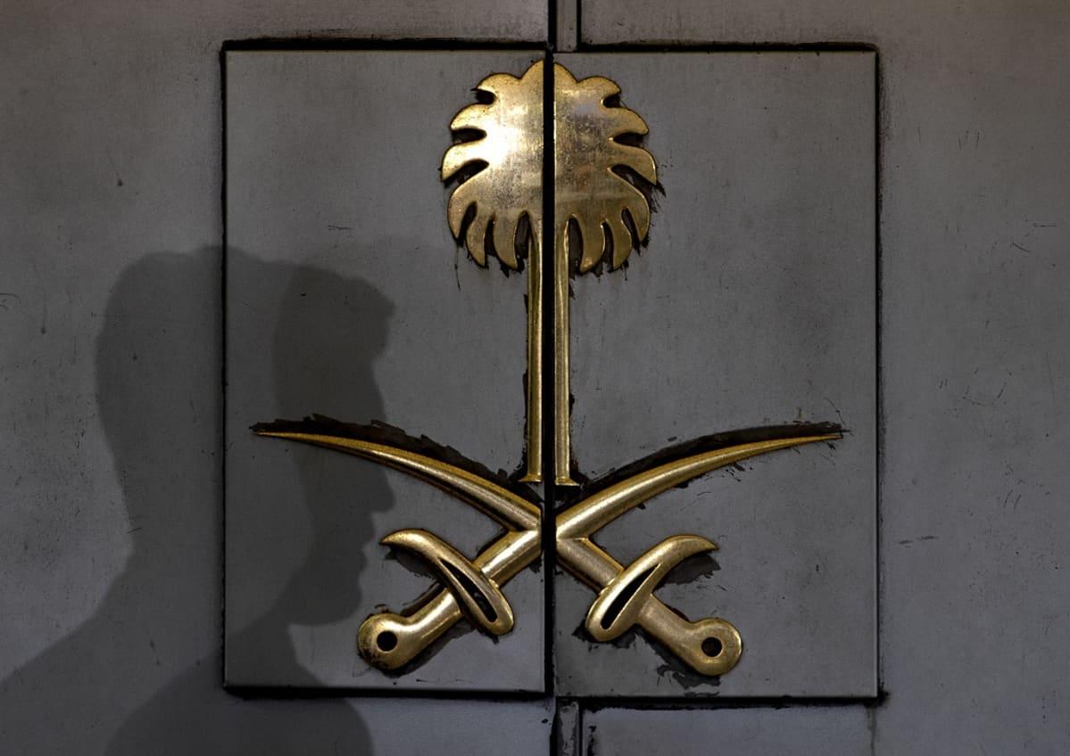 Ovessa on kullattu kohokuva palmusta ja kahdesta miekasta ristissä. Miehen varjo näkyy oven päällä.