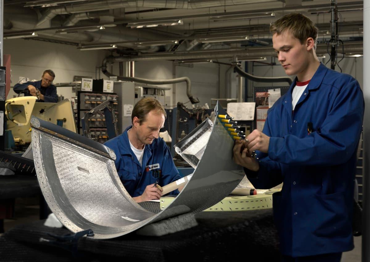 Kaksi haalareihin pukeutunutta työntekijää valmistaa lentokoneen osia.