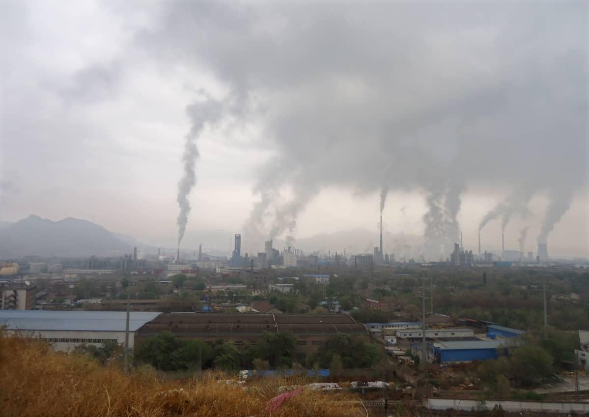 Tehtaita Kiinan Lanzhoussa. Useita harmaita savuvanoja pilvisellä taivaalla.