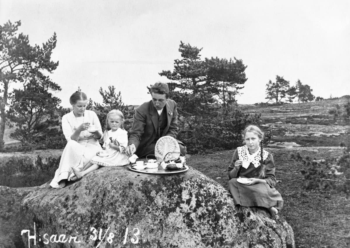 Perhe istuu kalliolla kahvikupit kädessä