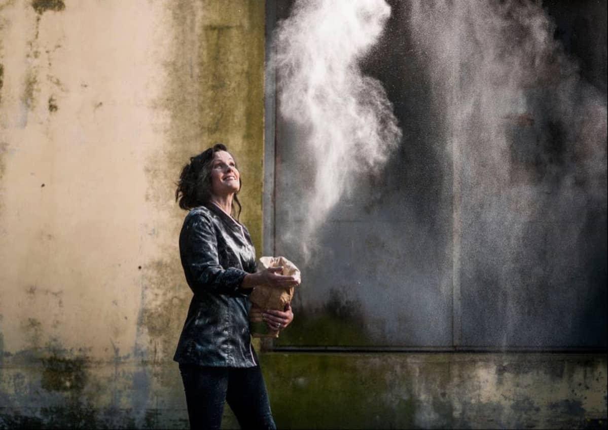 Jenni Höjer heittää jauhopussista jauhoja ilmaan.