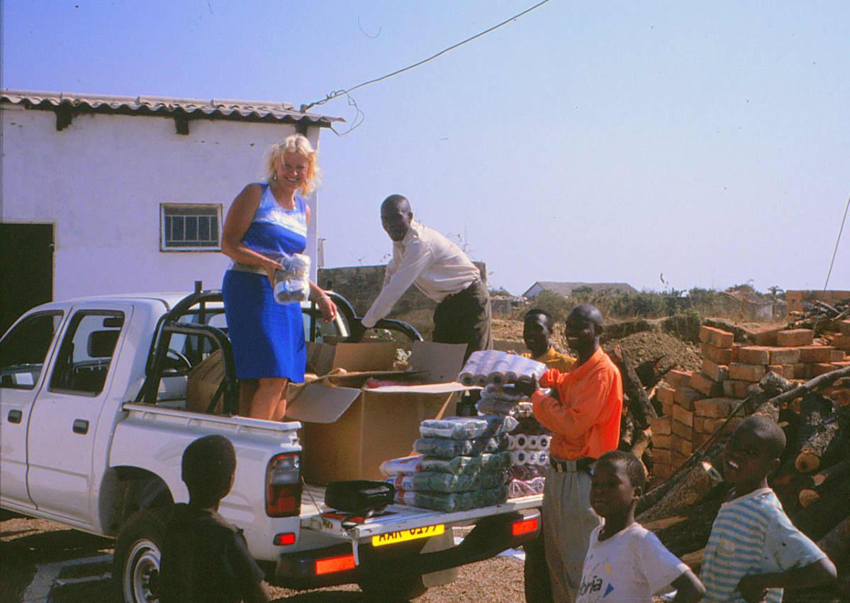 Tarja Helanen purkaa autokuormaa Sambiassa paikallisen väen kera.