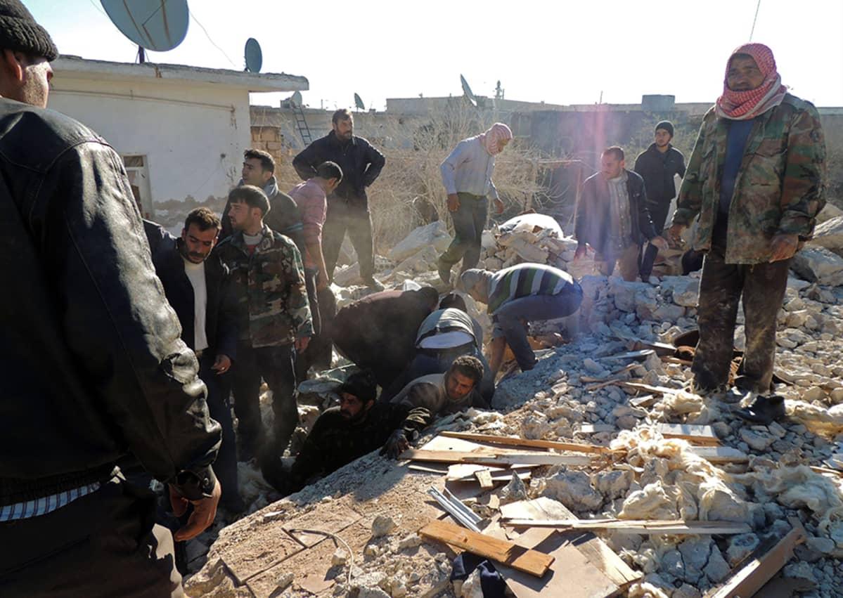Syyrialaiset etsivät pelastuneita hallituksen joukkojen tekemän ilmaiskun jälkeen Marean kaupungissa 22. joulukuuta.