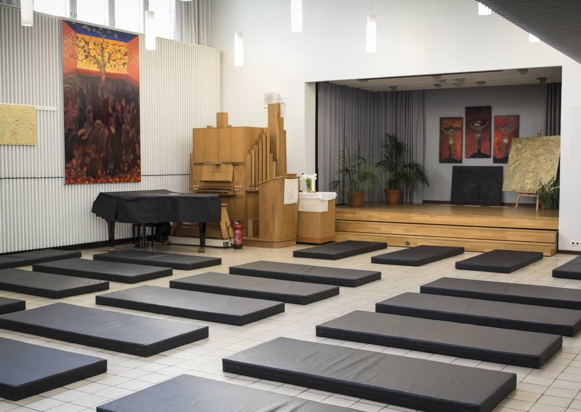 Hermannin diakoniatalon hätämajoitus, patjoja salin lattialla
