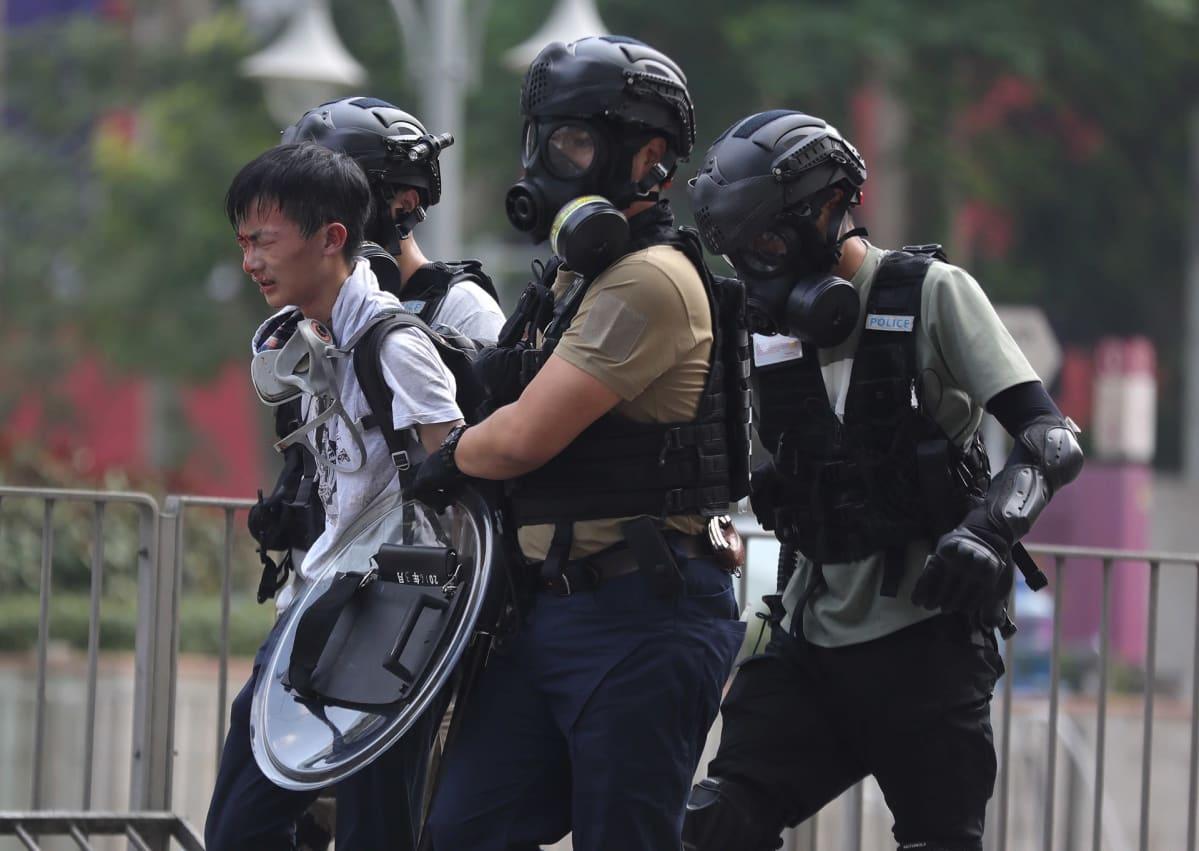 Kolme mellakkavarusteista poliisia taluttaa nuorta miestä.