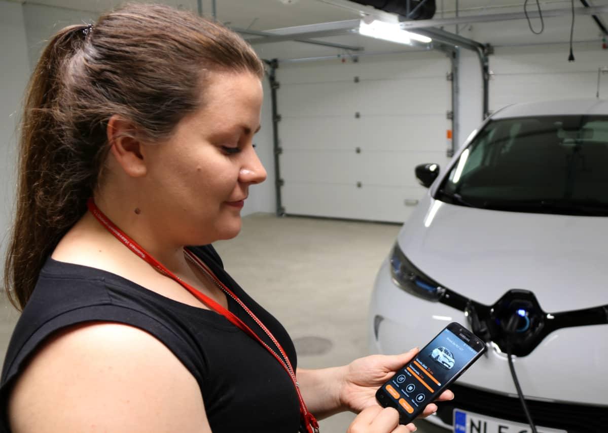 Penttilänrannan monisukupolvikorttelin yhteisökoordinaattori Minna Patama näyttää, kuinka yhteiskäytössä oleva sähköauto varataan puhelinsovelluksella.