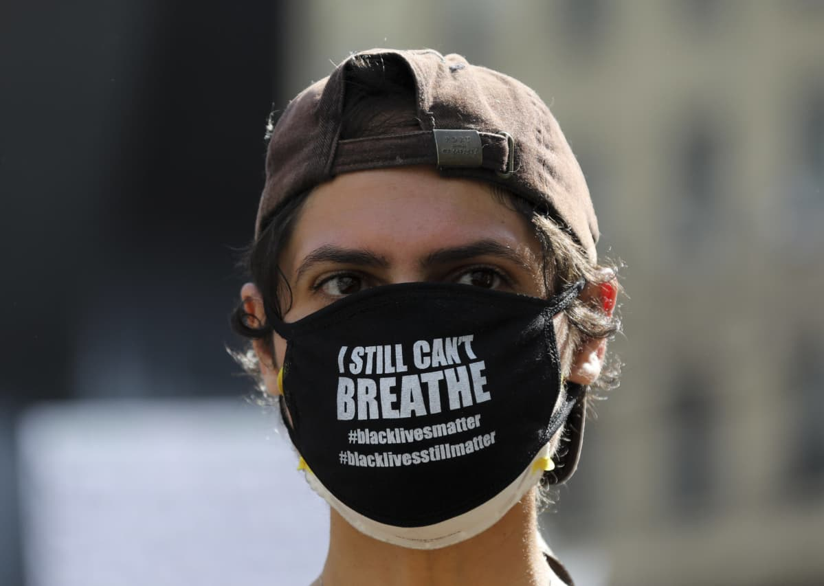 """New Yorkissa mielenosoittaja on pukeutunut mustaan kasvomaskiin, jossa lukee """"En vieläkään voi hengittää""""."""