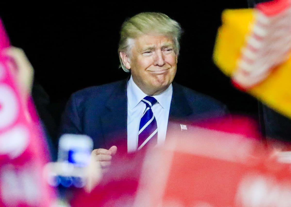 Trump hymyilee kuvan keskellä sinisessä puvussaan ja sinivalkoisessa solmiossa.