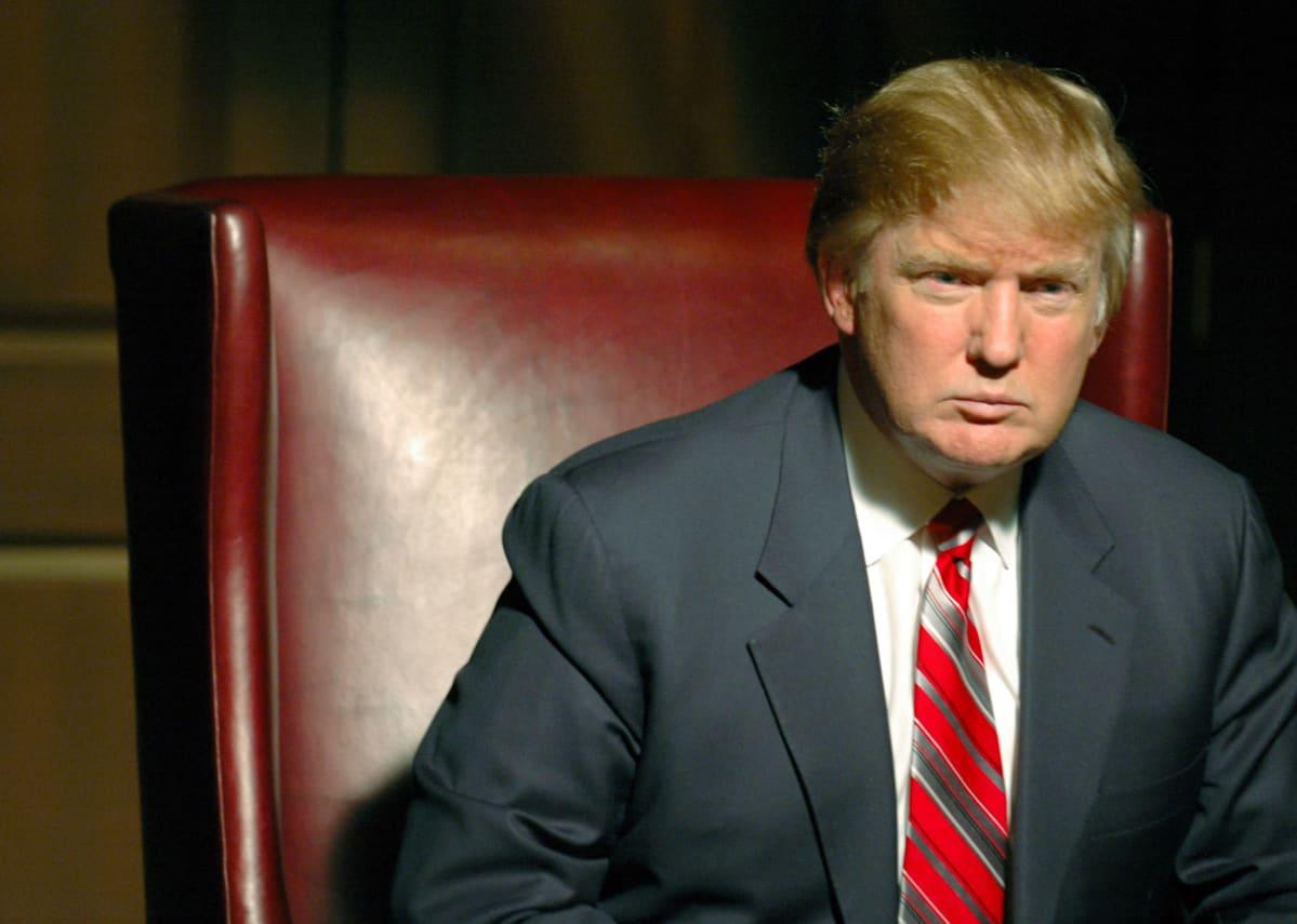 Donald Trump istuu tuimailmeisenä näyttävässä tuolissa tositv-sarjassa Diili.