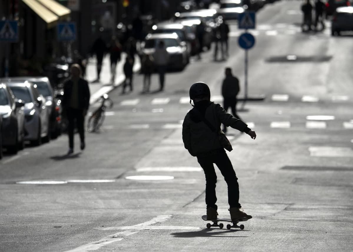 Nuori skeittaaja laskee alas katua, poika on kuvattu vastavalossa.