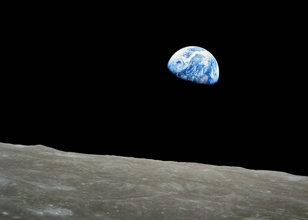 Maapallo avaruuden pimeydessä, edessä Kuun kamaraa.