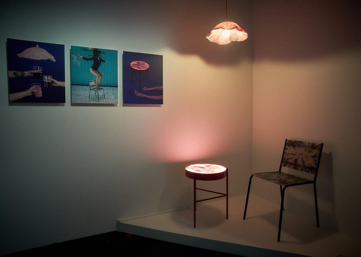 Valokuvia seinällä, valaisin, pöytä ja tuoli